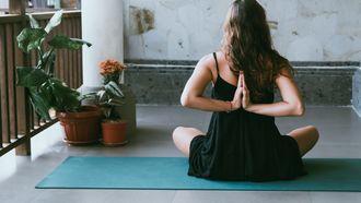 meisje doet yoga op balkon (de beste yoga-YouTubers voor thuis)
