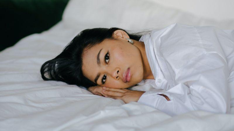 samen slapen / meisje ligt alleen op bed in witte blouse