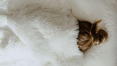 koud in bed / vrouw onder dekbed