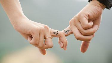 Twee handen met handtatoeages