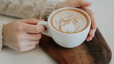 Vrouw houdt koffie in mok vast (Dit instagram account wil je volgen voor koffie recepten)