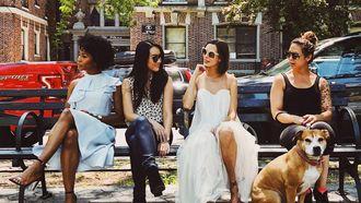 vier vriendinnen zitten op een bankje