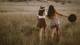 twee meisjes wandelen in het gras (type vriendin)