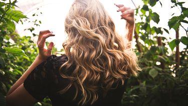 vrouw met lang haar in natuur (7x waarom je keratine wil gebruiken in je haar routine)
