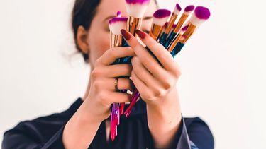 vrouw met make-up kwasten (net kunst: de Emoji make-up challenge op Tiktok )