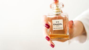 Vrouw met parfum in hand (hierom moet je vanaf nu parfum dragen naar bed)