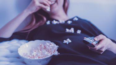 meisje eet popcorn in bed (de leukste films om te kijken op Valentijnsdag)