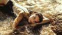 vrouw ligt in water op strand (10x dit herken je als je sterrenbeeld Vissen is)