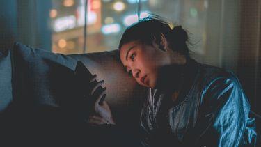 ghosten / meisje met telefoon in haar hand op de bank