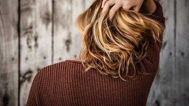 vrouw met hand in haar (de voordelen van sulfaatvrije shampoo)