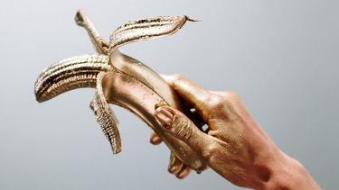 aftrekken / iemand houdt gouden banaan vast