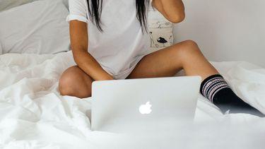 Meisje op bed met laptop (Met dit nieuwe videodatingplatform heb je binnen 1 minuut een nieuwe date)