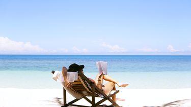 vrouw in ligstoel op strand (de mooiste instagram-accounts voor vakantiegevoel