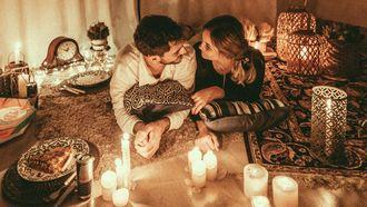 ideale partner vinden / koppel ligt tussen kaarsen in romantische setting