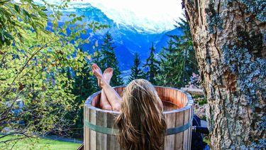 vrouw in bad in natuur (dit is jouw beste selfcare-moment volgens je sterrenbeeld)