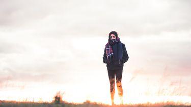 Meisje met jas aan lopend door de duinen (vitamine D)